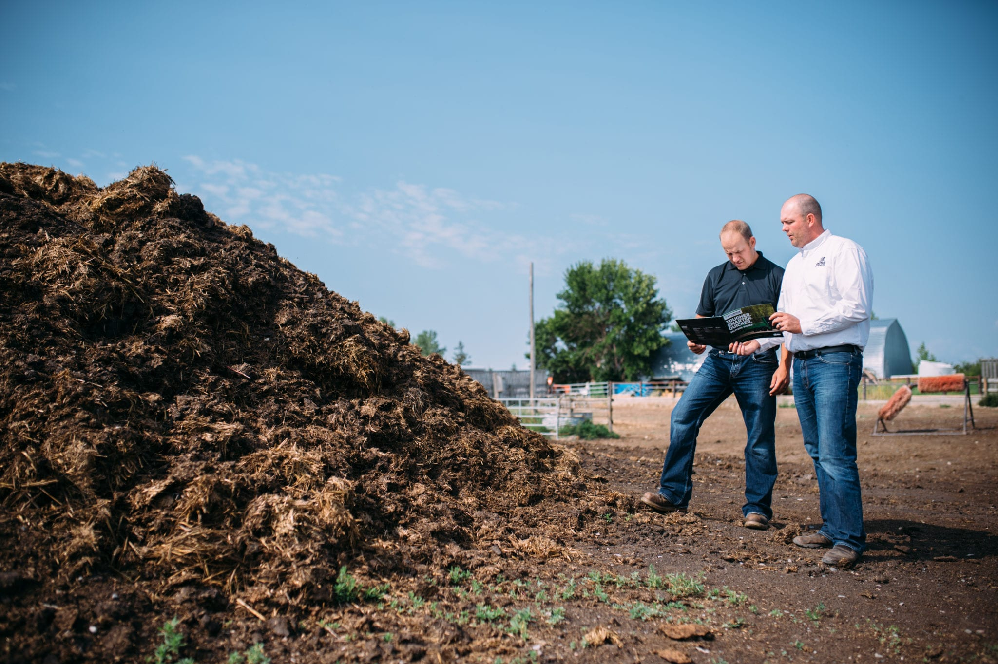 Two male farmers observing a pile of manure