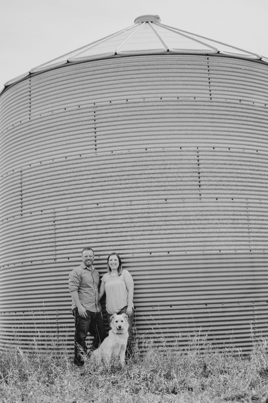 A man and woman standing in front of a grain silo with their dog